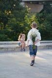 Un muchacho joven se está acercando a la muchacha con las flores foto de archivo libre de regalías