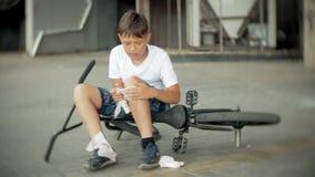 Un muchacho joven se sienta en un parque después de caer de una bici, calma el dolor en su rodilla, es un paseo peligroso de la b almacen de metraje de vídeo