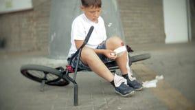 Un muchacho joven se sienta en un parque después de caer de una bici, calma el dolor en su rodilla, es un paseo peligroso de la b metrajes