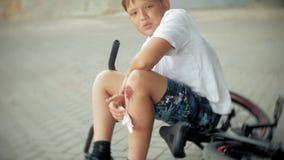 Un muchacho joven se sienta en un parque después de caer de una bici, calma el dolor en su rodilla, es un paseo peligroso de la b almacen de video