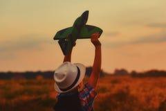 Un muchacho juega con un aeroplano modelo en la puesta del sol Fotos de archivo