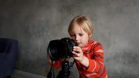 Un muchacho juega con una cámara real de la foto almacen de metraje de vídeo