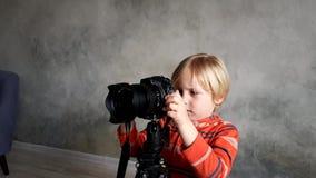 Un muchacho juega con una c?mara real de la foto metrajes