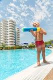 Un muchacho juega con una pistola de agua cerca de la piscina Imagenes de archivo