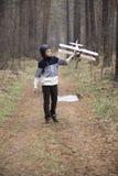 Un muchacho juega en el bosque con un avión del juguete juegos del otoño en el w imagenes de archivo