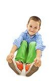 Un muchacho juguetón joven que se sienta en el piso Fotografía de archivo libre de regalías