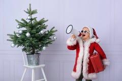 Un muchacho lindo vestido como Santa Claus, en una capa de zalea roja hermosa, imagenes de archivo