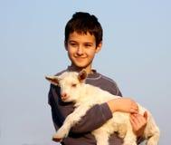 Un muchacho lleva una cabra del bebé Imagen de archivo libre de regalías