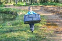 Un muchacho lleva una cesta plástica al lado de la charca niño con un la Foto de archivo