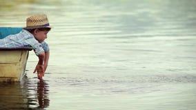 Un muchacho pequenito asperja el agua todo alrededor de sentarse en el barco de madera en el medio del lago almacen de metraje de vídeo
