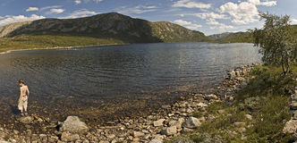 Un muchacho por un lago Fotos de archivo