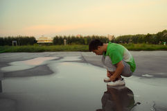Un muchacho puesto en cuclillas en el agua Fotos de archivo