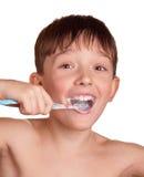 Un muchacho que aplica sus dientes con brocha después de baño Imágenes de archivo libres de regalías