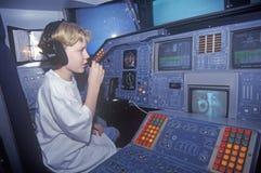 Un muchacho que asiste al campo del espacio en el George C Marshall Space Flight Center en Huntsville, Alabama, se sienta en la c Foto de archivo