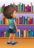 Un muchacho que busca un libro en la biblioteca Imagen de archivo