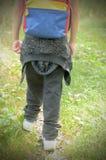 Un muchacho que camina en un alza en zapatillas de deporte y una mochila detrás de sus hombros Fotos de archivo