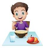 Un muchacho que come su desayuno en la tabla stock de ilustración