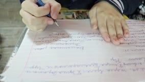 Un muchacho que escribe en el libro de ejercicio, haciendo su cierre de la preparación para arriba almacen de video