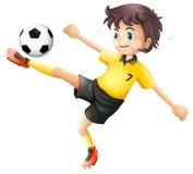 Un muchacho que golpea el balón de fútbol con el pie Imagen de archivo libre de regalías