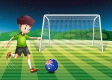 Un muchacho que golpea el balón de fútbol con el pie en el campo con la bandera de Aust Imágenes de archivo libres de regalías