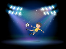 Un muchacho que golpea el balón de fútbol con el pie en la etapa Fotografía de archivo
