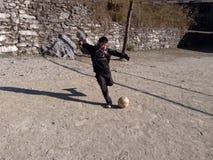 Un muchacho que golpea un fútbol con el pie Foto de archivo