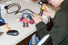 Un muchacho que hace un robot con el hierro de la soldadura eléctrica Imagen de archivo libre de regalías