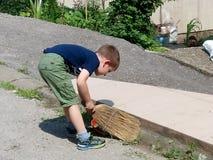 Un muchacho que hace tareas de hogar delante de un muchacho casa-digno Foto de archivo libre de regalías