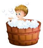 Un muchacho que juega con las burbujas dentro del barril grande Fotos de archivo libres de regalías