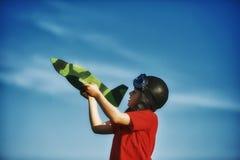 Un muchacho que juega con un modelo de madera del avión Imagen de archivo