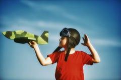 Un muchacho que juega con un modelo de madera del avión Fotografía de archivo libre de regalías