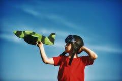 Un muchacho que juega con un modelo de madera del avión Imagenes de archivo