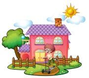 Un muchacho que juega delante de la casa rosada grande Fotografía de archivo