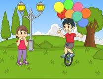 Un muchacho que juega el unicycle y que lleva a cabo el baloon delante de una muchacha en la historieta del parque Fotografía de archivo libre de regalías