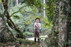 Un muchacho que juega en un bosque tropical en el valle de Danum en Borneo Imagen de archivo