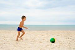 Un muchacho que juega a fútbol en la playa Foto de archivo libre de regalías