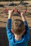 Un muchacho que lleva a cabo los anillos del metal imagenes de archivo