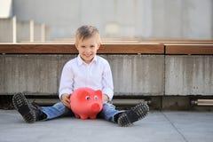Un muchacho que lleva a cabo un moneybox rojo imágenes de archivo libres de regalías