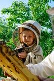 Un muchacho que lleva un traje protector en un colmenar cerca de una colmena con las abejas Foto de archivo libre de regalías