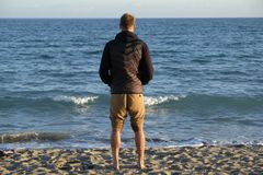 Un muchacho que mira panorama sobre el horizonte de mar en la playa - estación del invierno en la puesta del sol fotos de archivo libres de regalías