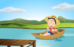 Un muchacho que rema un barco Imagenes de archivo