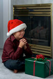 Un muchacho que ruega para el regalo fotos de archivo