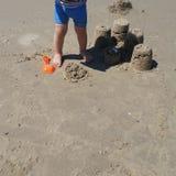 Un muchacho que se coloca cerca de las torres de la arena que él construyó con sus juguetes plásticos en la playa imagen de archivo