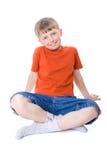 Un muchacho que se sienta con las piernas cruzadas Fotografía de archivo libre de regalías