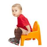 Un muchacho que se sienta en el crisol imagenes de archivo