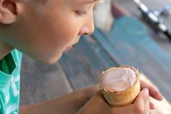 Un muchacho que se sienta en las escaleras de madera y que come el helado foto de archivo