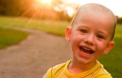 Un muchacho que sonríe en la cámara en el fondo de la puesta del sol Fotos de archivo