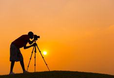 Un muchacho que toma una foto durante puesta del sol Foto de archivo