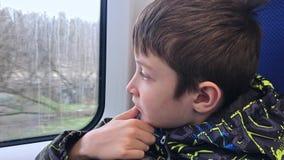 Un muchacho que viaja en tren, ?l est? mirando a trav?s de la ventana almacen de metraje de vídeo