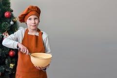 Un muchacho rubio en la ropa anaranjada del cocinero, soportes cerca de un árbol de navidad adornado con una taza en sus manos Fo fotos de archivo libres de regalías
